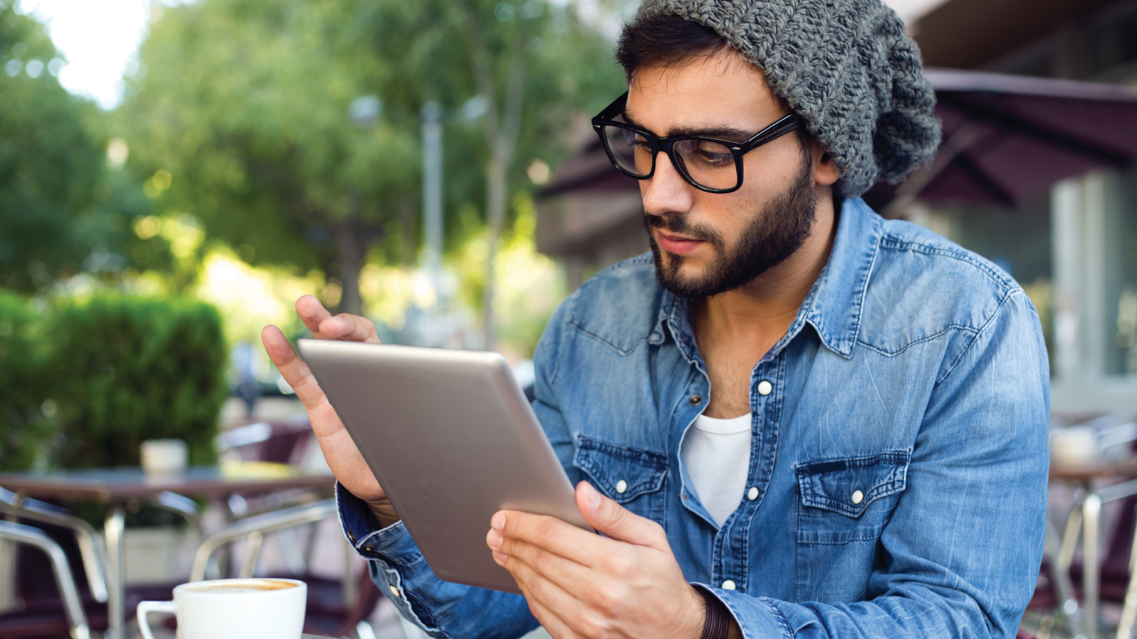 Man enjoying coffee while checking his account on a tablet